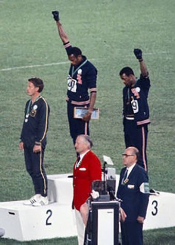 American sprinters John Carlos and Tommie Smith's black power salute at the 1968 Mexican Olympic Games. By Angelo Cozzi via Wikimedia Commons, CC BY-SA