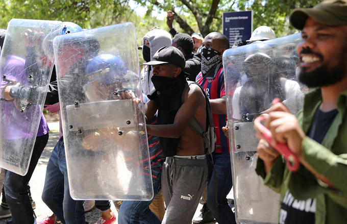 Students use shields belonging to private security during clashes with police at Wits University. Siphiwe Sibeko/Reuters