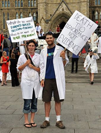 Does wearing a lab coat and holding a witty jargon-laden sign send the right message? Shutterstock