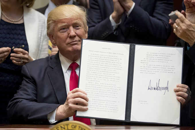 President Donald Trump holds the signed Education Federalism Executive Order. Wednesday, April 26, 2017. AP Photo/Andrew Harnik